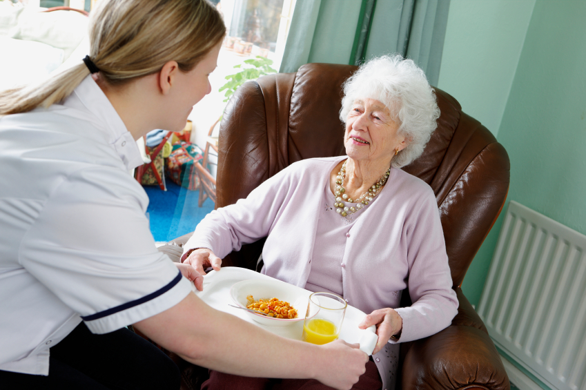 carer helps her elderly pactient by making sure she eats her a meal